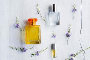 Perfumes y frascos de perfume sobre un fondo de madera blanca foto