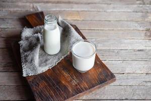 botellas y vasos de leche en una mesa de madera foto