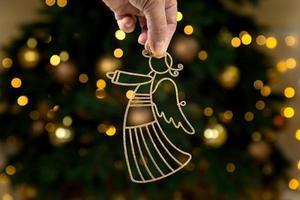 ángel dorado de navidad en la mano sobre fondo de árbol foto