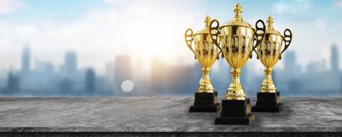 1er campeón otorga el mejor premio y concepto ganador copa de campeonato o trofeo ganador en mesa de madera con fondo de ciudad azul suave y bokeh foto