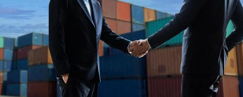 concepto de negocio de carga de exportación e importación cerca de la mano de los empresarios dándose la mano en la terminal de contenedores industriales transporte marítimo y logística acuerdo exitoso y éxito en el contrato foto