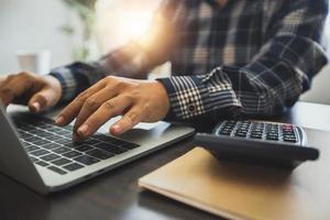 Cerrar la mano del empresario utilice el número de registro y el presupuesto financiero en la computadora portátil después de calcular con la calculadora de finanzas y el contador con el concepto de tecnología foto
