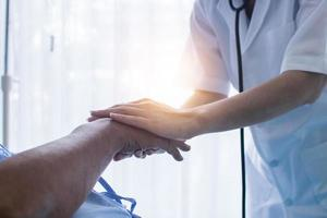 Close up hand of doctor encourages elderly patient to fight  and hope to get well photo