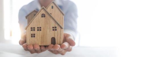 Concepto de inversión inmobiliaria y de propiedad cerca de la mano del empresario sosteniendo el modelo de madera de la casa en la cubierta horizontal foto