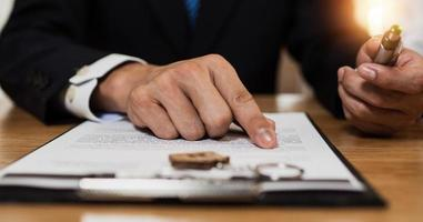 Verifique y lea el contrato detenidamente antes de firmar la mano cercana del empresario leyendo y verificando el documento comercial y firme en papel foto
