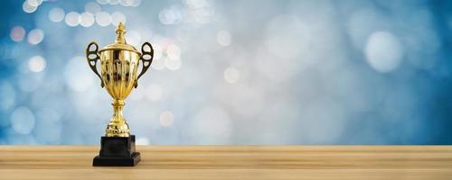 1er campeón otorga el mejor premio y concepto ganador copa de campeonato o trofeo ganador en mesa de madera con fondo azul suave y bokeh foto