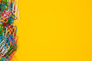 Colorful paper clips on yellow background photo