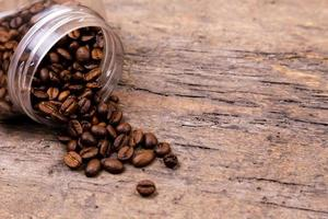 Aromatic coffee beans dropped out of a glass jar photo