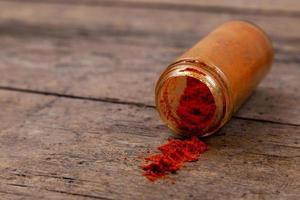 Chile colorido polvo de especias esparcidas de botella sobre fondo de madera foto