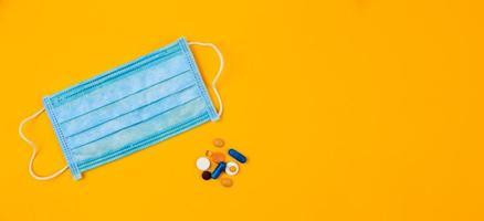 Máscara médica protectora azul sobre fondo amarillo rodeado de pastillas de colores foto