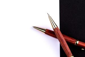 Luxury pen and mechanical pencil in wood and gold with a white sheet of paper photo