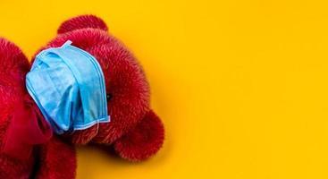 Oso de peluche rojo solitario en una máscara médica protectora sobre un fondo amarillo foto