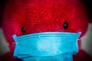 Oso de peluche rojo solitario en una máscara médica protectora foto