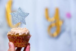 Mano de niña sostiene cupcake de arándano con estrella plateada brillante foto