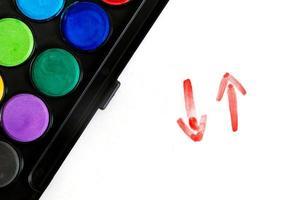 Flecha roja pintada a mano con trazos de pincel aislado en el fondo blanco. foto