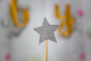 Decoración de estrella plateada con purpurina sobre fondo gris foto