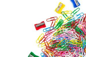 A lot of colored paper clips and pencil sharpeners on a white background photo