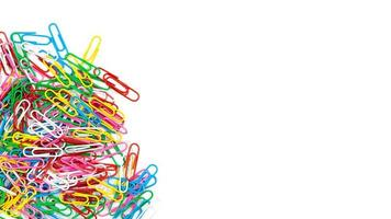 Many colorful stationery paper clips on a white background photo