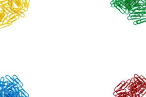 Red, yellow, blue and green stationery clips on a white background photo