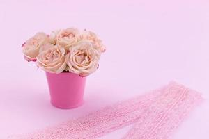 A bouquet of beautiful roses stands in a small bucket on a lace ribbon photo