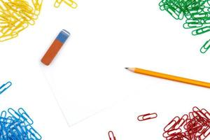 Pencil, eraser and paper clips on a white background photo
