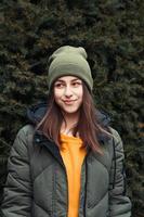 Retrato vertical de una hermosa niña sonriente en un suéter amarillo y sombrero caqui foto