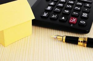 Close up of Fountain pen and calculator and yellow paper house on wooden table background photo