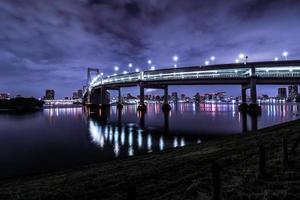 tokio, noche, ciudad, scape, en, odaiba, con, arco iris, puente foto