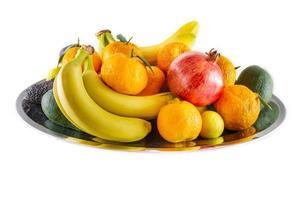 Plato surtido de frutas y verduras de banano, granada, limón, mandarina y aguacate. foto