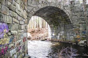 River going under a stone bridge in the spring photo