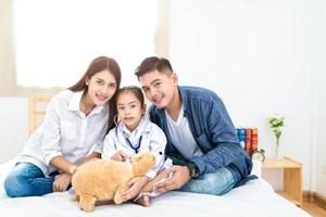 Cute little Asian girl dressed like a doctor at home photo