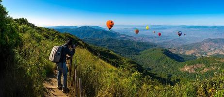 Professional photographer takes landscape photos on a mountain with hot air balloons in the background