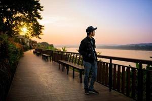 Viajero caminando sobre un puente de madera cerca del río al atardecer foto