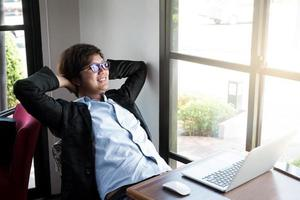 Young businessman relaxing at his desk in coffee shop photo