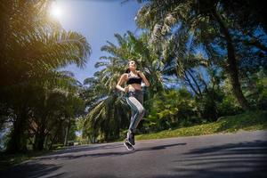 Pretty woman jogging in the park, running outdoors in nature photo