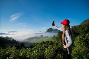 Mujer tomando fotos selfie en la montaña con niebla de fondo, paisaje en la provincia de Mae Hong Son, Tailandia