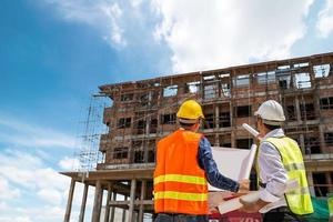 Businessman and engineer looking at a building blueprint at a high rise building construction site photo