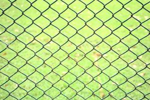 Chain link pattern abstract fence with green grass field background photo