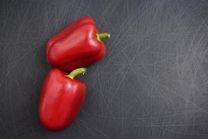 Closeup colorido elegante campana roja o pimientos dulces planos yacía sobre fondo negro textura rayada grunge foto