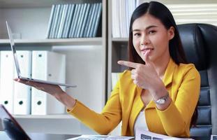 Mujer de negocios asiática sostiene una computadora portátil sentada en la oficina y sonriendo felizmente foto