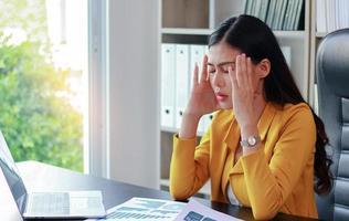 Retrato de mujer asiática en traje amarillo sentado en la oficina pensando en marketing foto