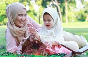 Madre musulmana enseña a su hija a leer felizmente el Corán en el parque en verano. foto