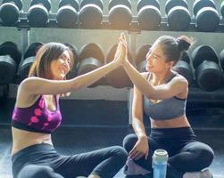 Dos hermosas chicas asiáticas descansaron después de hacer ejercicio en el gimnasio. foto