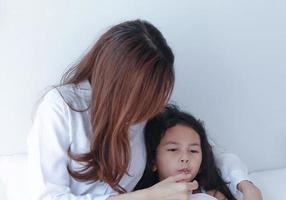 madre asiática midiendo la temperatura de su hija foto