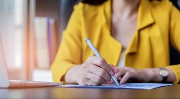 mano de la dama de negocios está firmando un contrato de cooperación comercial foto