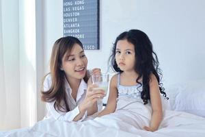 Mother is giving her daughter milk in the morning photo