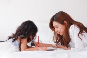 Asian mother is teaching her daughter homework at home on vacation photo