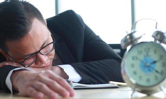 Portrait of young Asian businessman sleeping on the desk in weariness photo