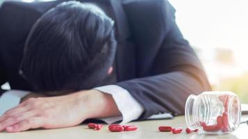 Asian businessman sleeps on his desk in fatigue with scattered painkillers on the table photo
