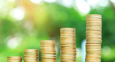 Pile of coins stacked against blurred green background photo